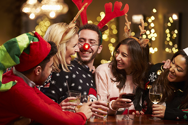 Group Of Friends Enjoying Christmas Drinks In Bar Smiling Wearing Christmas Hats